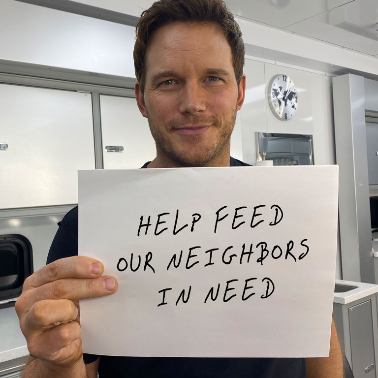 Chris Pratt holding sign saying Help Our Neighbors In Need
